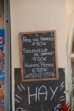 Pizarra con ofertas: Paté de perdiz 7,50€; Solomillo al jerez 9,50€; Huevos rotos: 6,50€; mollejas