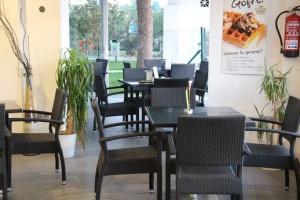 mesas y sillas del interior en color negro. También hay una terraza externa con sillas azules.