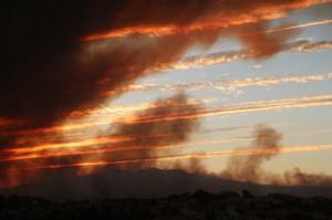 El humo se confunde con las nubes de la puesta de Sol dando una extraña belleza