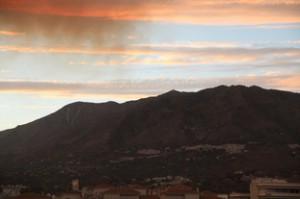 Puesta de Sol. El pueblo que se ve es Mijas. Cielo azul, nubes rojizas, pero si se fijan en la parte izquierda hay humo.