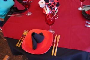 Detalle de los cubiertos. Aquí vemos plato rojo y servilleta negra. Mantel rojo, sobre mantel negro y copas rojas. En una foto posterior verán que los platos son negros con servilleta roja.