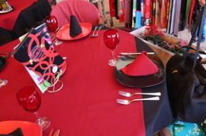 A un lado de la mesa platos negors con servilletas rojas, al otro, plato rojo con servilleta negra.