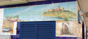 En la pared que mira al este hay u cuadro de cerámica bastante bonito con imágenes de Fuengriola, por ejemplo el Castillo y los bolichitos, pero que se ven estropeados por esa fea puerta azul.