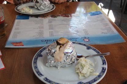 Envuelto en papel de alumino hay una patata asada, dentro de la cual hay pisto y en la cima hay un mejillón