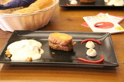 Bandeja de cerámica negra. A la derecha huevos cocidos de codorniz y pimiento rojo. En el centro pan frito con jamón serrano y queso fundido. Y a la izquierda algo parecido a un canelón con bechamel por encima y dentro rabo de toro.