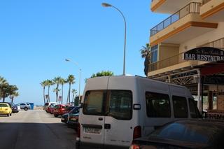 A la derecha se ve el letreo del restaurante. La furgoneta blanca lo tapa casi entero, pero al fondo están las plameras que señalan la ubicación de la playa. Ya ven que estñá muy cerca.