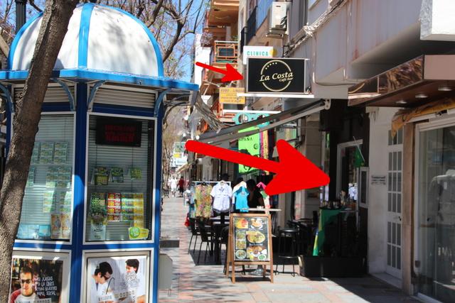 La flecha de arriba indica el letrero y la de abjo la puerta de entrada. El kiosco de la ONCE es una buena pista para encontrarlo