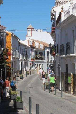 Una calle típica y al fondo la torre campanario con sus rayas laterales que dan un toque de color