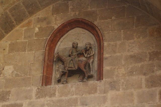 Detalle de la hornacina encima de la puerta:San Martín parte su capa.