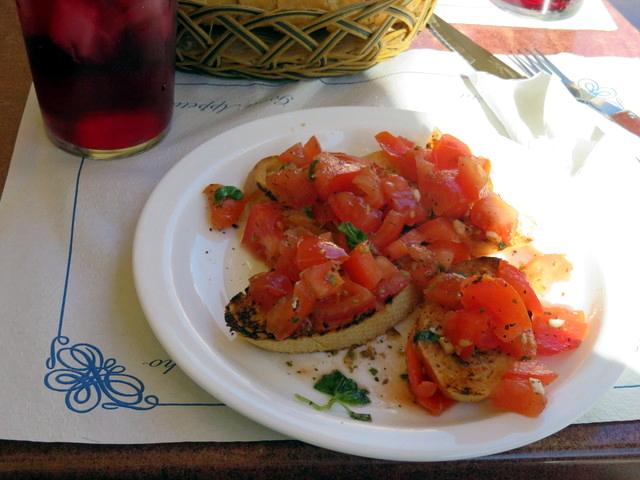 Bruschetta, con pan tostado, tomate picado, ajo y alguna otra especia.