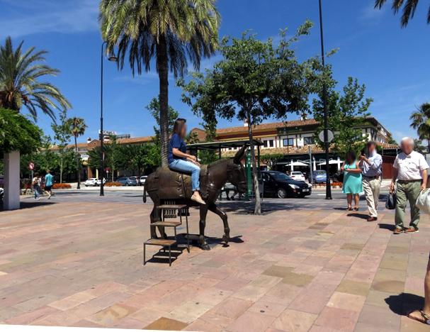 Turistas montando en el burrito de bronce. (Observen que hay escaleras para hacerlo).