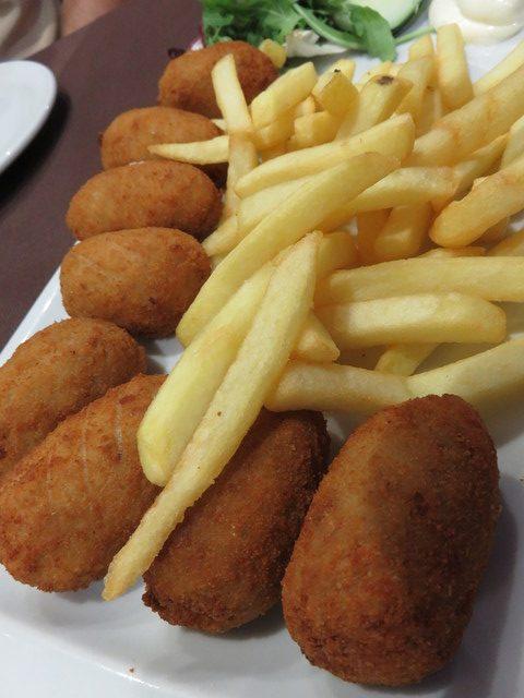 Ración de croquetas, acompañadas de patatas fritas.